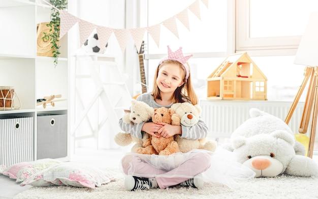 Smiling little girl hugging teddy bears
