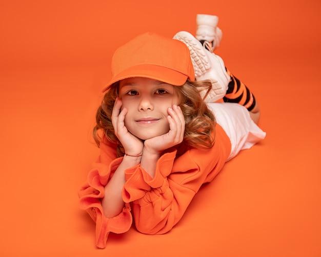 オレンジ色の背景のスタジオの床に横たわっている帽子とファッショナブルな服を着て笑顔の少女。モックアップ