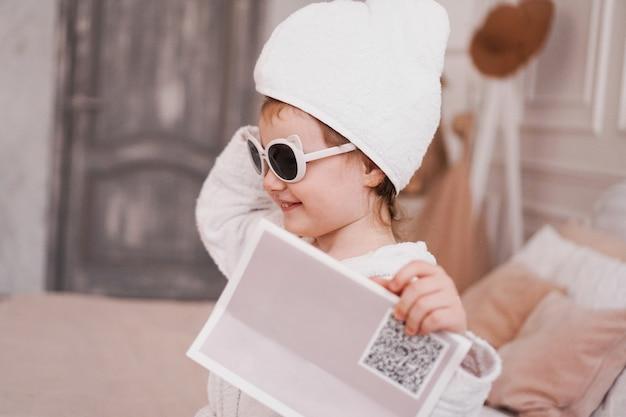 목욕 후 흰색 목욕 가운에 웃는 어린 소녀. 화이트톤의 아늑한 인테리어. 위생 및 아기 패션 개념입니다. 그녀는 선글라스를 쓰고 있고, 소녀는 손에 잡지를 들고 있다