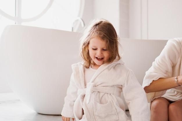 목욕 후 흰색 목욕 가운에 웃는 어린 소녀. 화이트톤의 아늑한 인테리어. 위생 및 베이비 패션 컨셉