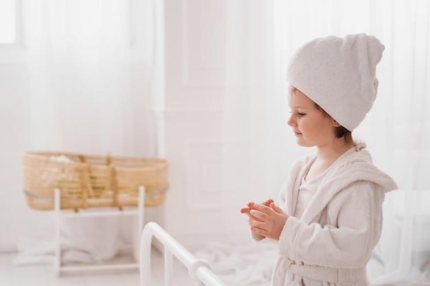 入浴後の白いバスローブで小さな女の子の笑顔白い居心地の良いインテリア