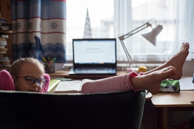 Улыбающаяся маленькая девочка в очках лежит в кресле во время онлайн-урока в школе