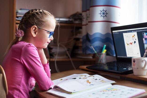 Улыбающаяся маленькая девочка в очках учится онлайн и использует свой ноутбук дома