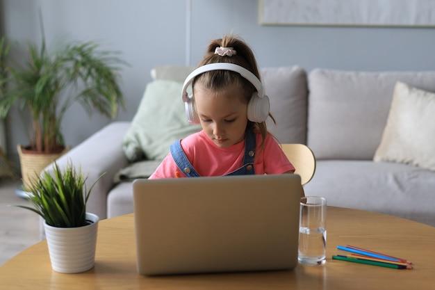 Улыбающаяся маленькая девочка в наушниках пишет от руки онлайн, используя портативный компьютер дома, милый счастливый маленький ребенок в наушниках принимает уроки или занятия в интернете на пк.