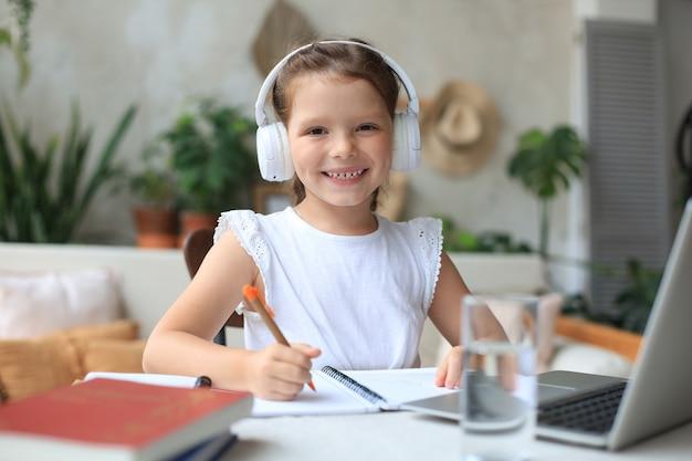 헤드폰을 끼고 웃고 있는 어린 소녀는 집에서 노트북을 사용하여 온라인으로 공부하고, 이어폰을 낀 귀여운 행복한 어린 아이는 pc에서 인터넷 웹 수업이나 수업을 받습니다.