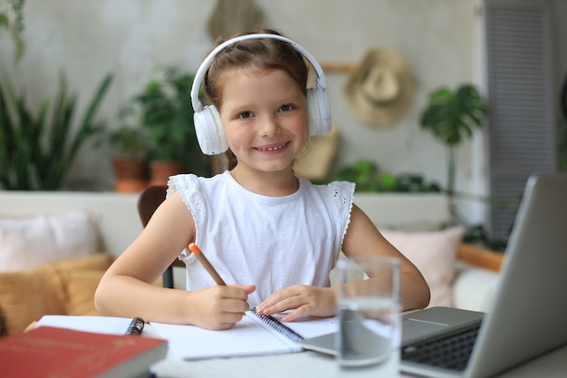 헤드폰을 끼고 웃고 있는 어린 소녀가 집에서 노트북을 사용하여 온라인으로 공부하고, 이어폰을 낀 귀여운 행복한 어린 아이는 인터넷 웹 수업이나 pc 수업을 받습니다.