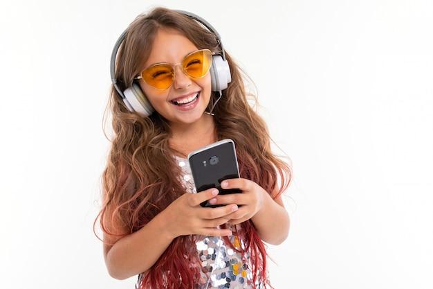 Улыбающаяся маленькая девочка в оранжевых очках держит телефон и наушники