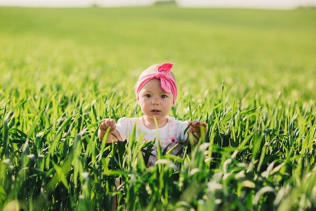Улыбающаяся маленькая девочка в белом платье идет в поле с зеленой травой.
