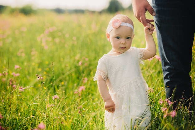 Улыбающаяся маленькая девочка в белом платье идет в поле с полевыми цветами.
