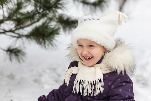 크리스마스 트리 근처 눈 속에서 겨울 옷을 입고 웃는 어린 소녀