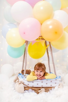Smiling little girl is sitting in basket decorative balloon