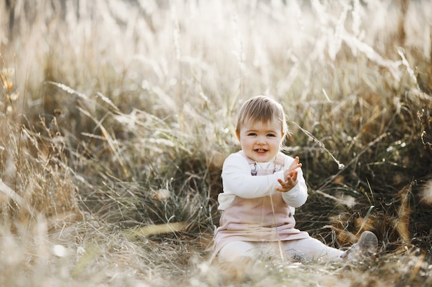 Smiling little girl is sitting on the lawn in the sunlight