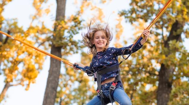 Улыбающаяся маленькая девочка прыгает на батуте со скакалкой в осеннем парке приключений