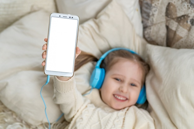 Smiling little girl kid in headphones shows white blank screen for text space