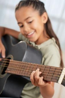 Улыбающаяся маленькая девочка учится играть на гитаре во время урока дома