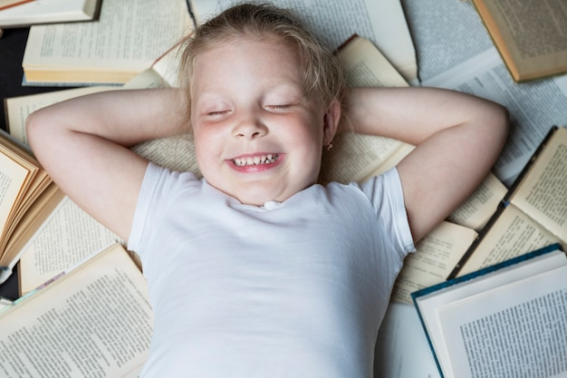 A smiling little girl lies with closed eyes on a pile of open books. top view. education and training. close-up.