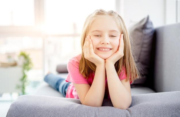 明るいアパートのソファーに横になっている笑顔の少女