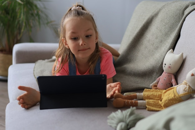 タブレットで面白いアプリケーションを使用して、オンラインゲーム、webサーフィン情報を再生するソファに横たわっている小さな女の子の笑顔。
