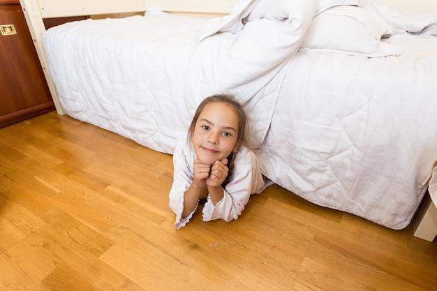 Улыбающаяся маленькая девочка, лежащая под кроватью дома и смотрящая в камеру