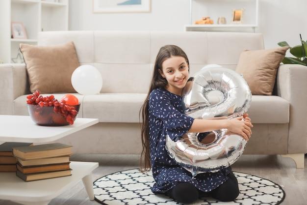 행복한 여성의 날에 웃고 있는 어린 소녀가 거실에서 8번 풍선을 들고 바닥에 앉아 있다