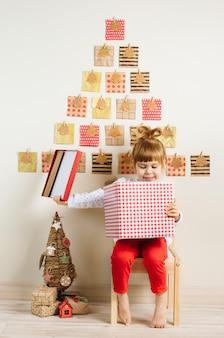 Улыбающаяся маленькая девочка открывает подарочную коробку возле рождественского адвент-календаря ручной работы в детской комнате
