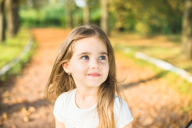 Smiling little girl in the park looking away