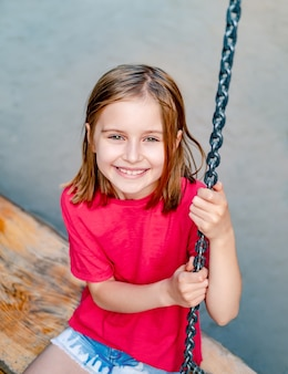 Smiling little girl on park swing on playground, top view