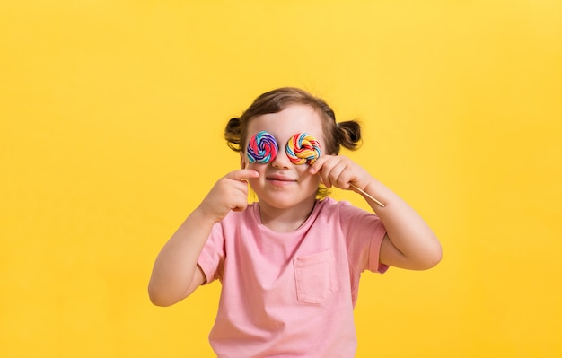 A smiling little girl in a pink t-shirt with ponytails covers her eyes with lollipops