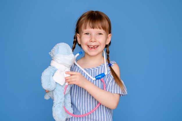 Smiling little girl playing a doctor and listening to a teddy bear with a stethoscope isolated on a blue wall. veterinary clinic game. the concept of the future profession.