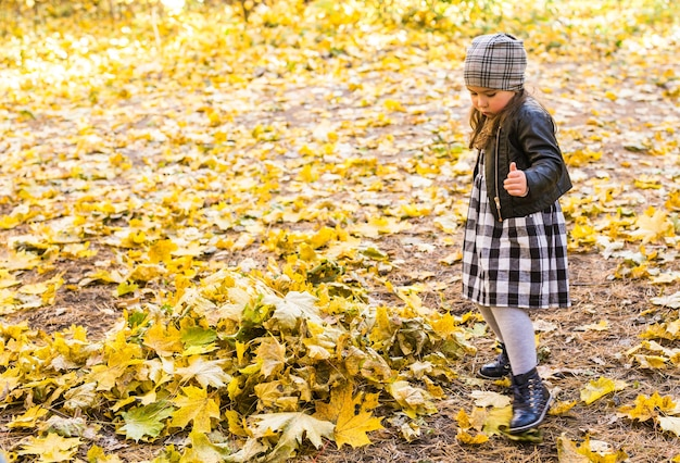 Smiling little girl playing yellow leaves in autumn park