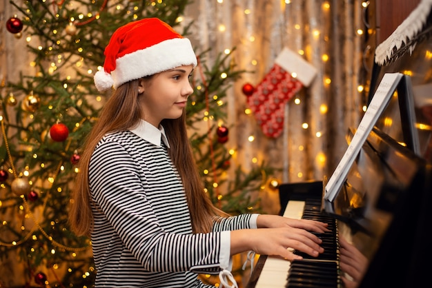 Smiling little girl in red santa hat playing beautiful song on the piano