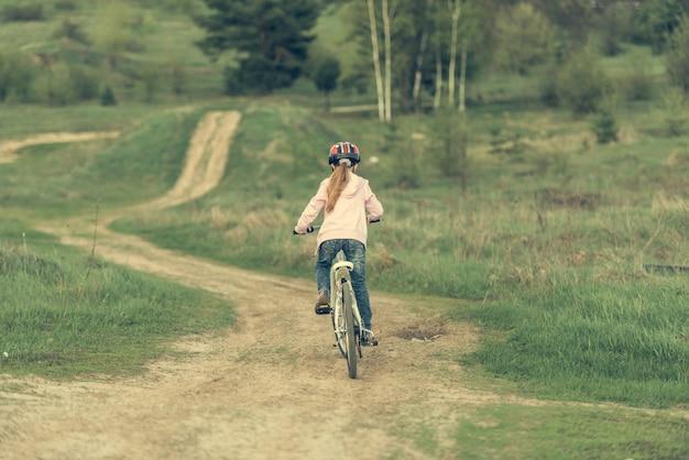 自転車に乗って笑顔の女の子が背を向けた