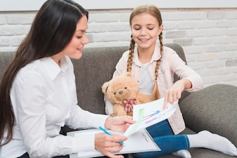 Smiling little girl showing drawn drawing paper to the female psychologist