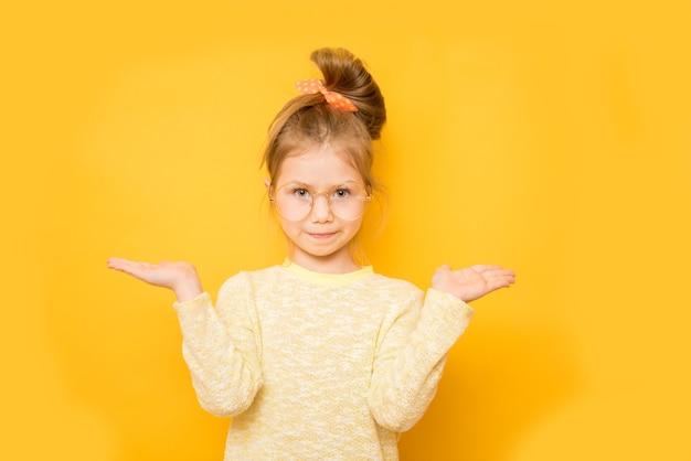 Улыбающаяся маленькая девочка показывает весы на руках на желтой стене. копировать пространство