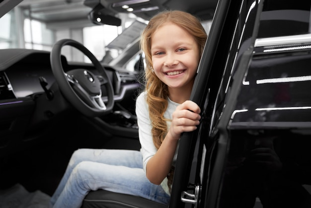 Smiling little girl sitting in driver's seat of new car.