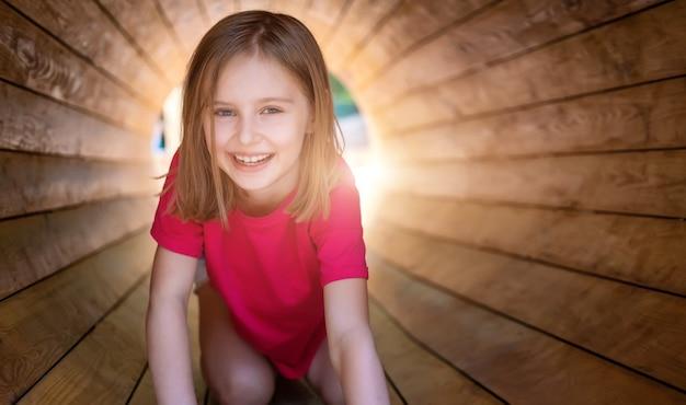 Улыбающаяся маленькая девочка, сидящая в деревянной трубе в парке