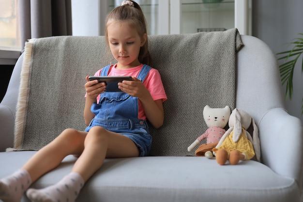 スマートフォンで面白いアプリケーションを使用して、オンラインゲーム、webサーフィン情報を再生するソファに座っている小さな女の子の笑顔。