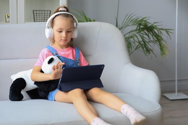 タブレットで面白いアプリケーションを使用して、オンラインゲーム、webサーフィン情報を再生するソファに座っている小さな女の子の笑顔。