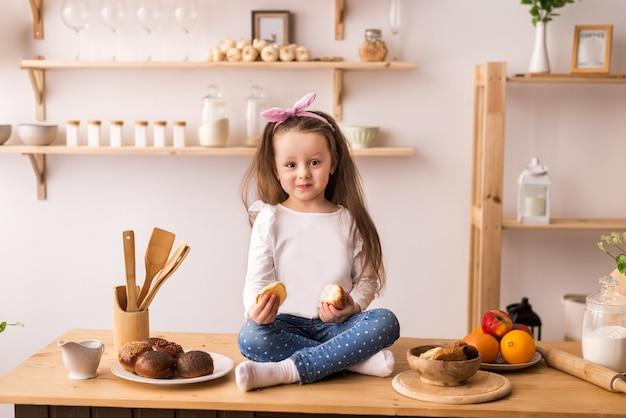 Улыбающийся маленькая девочка, сидя на рабочей поверхности кухни в ожидании завтрака. веселая и озорная девушка на кухне.