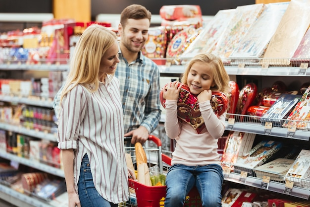 Smiling little girl sitting on a shopping cart and choosing candy with her parents at the supermarket