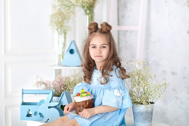 Smiling little girl sitting at white table in kitchen with easter panettone. easter interior. spring home decor. happy family getting ready for easter. easter cake in hand of little girl. bunny, eggs