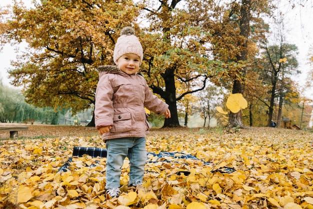 Bambina sorridente che sta nella foresta di autunno