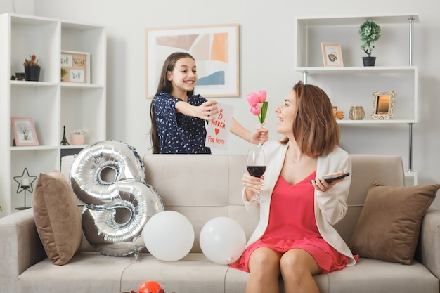 소파 뒤에 서 있는 웃고 있는 어린 소녀는 거실에서 전화와 와인 한 잔을 들고 웃는 엄마에게 엽서와 함께 frowers를 제공합니다