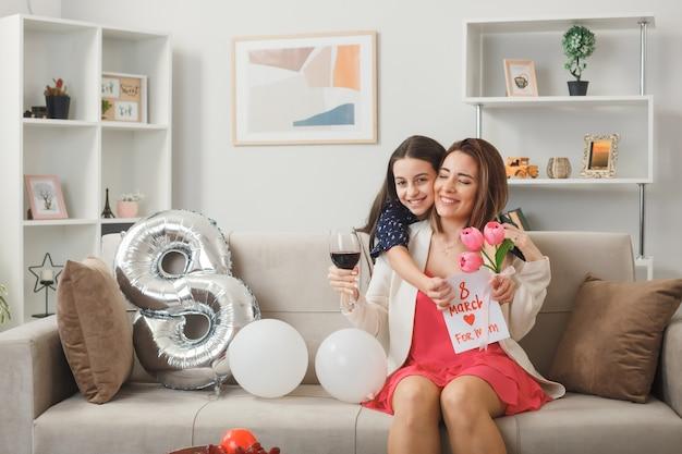 Sorridente bambina in piedi dietro il divano con in mano fiori con biglietto di auguri ha abbracciato la madre sul divano durante la felice festa della donna in soggiorno