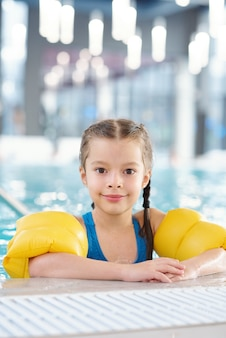 Smiling little girl in swimwear looking at you after swimming lesson in pool while standing in front of camera against in sports or leisure center