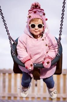 Smiling little girl , swinging on a swing in the park. girl play on school or kindergarten yard.