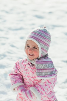 雪の上を歩いてあなたの人生で初めて小さな女の子を笑顔