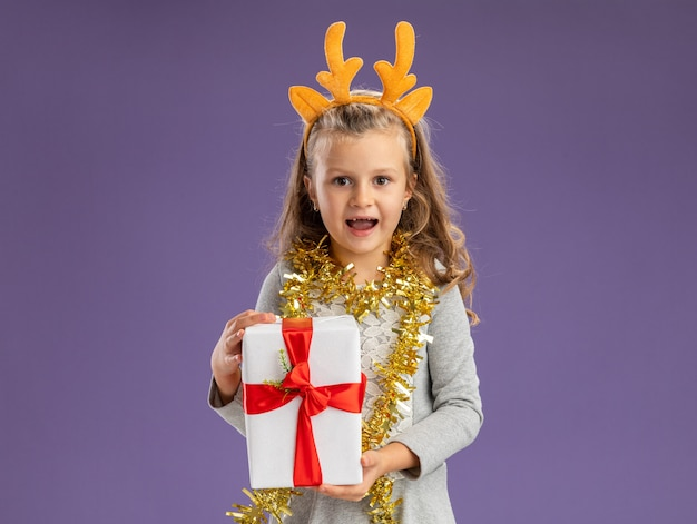 Smiling little girl wearing christmas hair hoop with garland on neck holding gift box isolated on blue wall