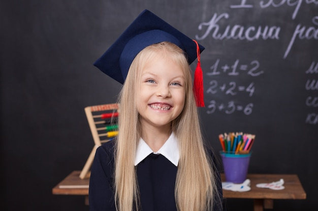 Smiling little girl wearing a master's graduation cap at school