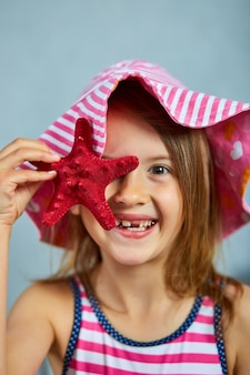 Smiling little girl wearing pink hat holding starfish. summer vacation concept with close up face portrait of beautiful girl.